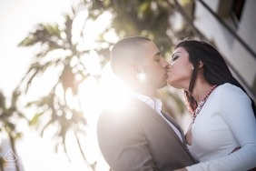 Engagement portrait shot straight into the sun of a kissing couple in Miami Florida