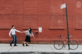 Urban engagement portrait in Spain with a couple holding hands against a red brick building with a bicycle