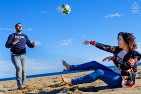 Valencia engaged couple having fun together at the beach playing volleyball for their engagement portrait