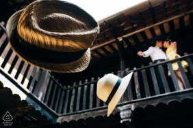 Ho Chi Minh engagement photograph of a young couple throwing their hats from the second floor