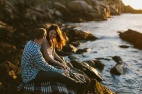 Zdjęcie sesji zaręczynowej Boston na skałach przy plaży w pobliżu zachodu słońca