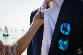 A young woman grabs the collar of her fiancé has she is reflected in the sunglasses hanging from his coat pocket in China