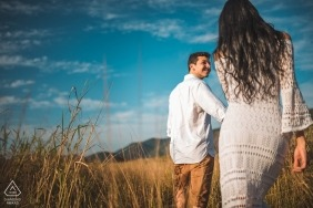 Rio de Janeiro Engagement Photos of couple walking in tall, dry grass in the warm sun