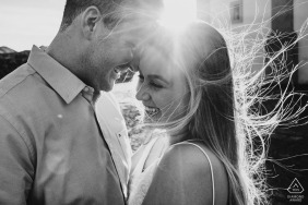 Tight black and white engagement portrait shot into the sun on a windy day