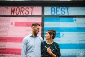 Humorous engagement portrait of a couple with Worst/Best painted wall | Washington DC photographer pre-wedding pictures