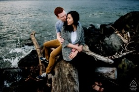 Washington engagement images of a couple sitting on rocks at the ocean   Seattle photographer pre-wedding session