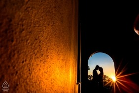 Archway engagement pictures of a couple in the warm sun flares  | Argentina photographer pre-wedding shoot