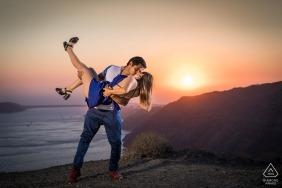 Mariage de photographe de mariage sud de l'Égée portrait d'un couple plongeant sur la plage au coucher du soleil | Photos pré-mariage à Santorin