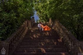 Vereinigtes königreich vor der hochzeit verlobungsfotos von einem paar sitzen auf einer großen treppe in den bäumen | Paarfotografiesitzung