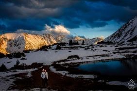 Photos d'engagement de montagne d'un couple dans la neige au bord du lac | Photographe de CO avant le mariage