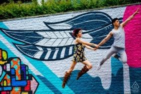 Un couple vole dans les airs lors de leur séance de portrait de fiançailles en milieu urbain à Arlington, VA