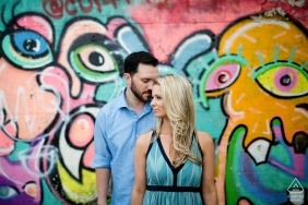 New England wedding photographer engagement portrait of a couple with a graffiti mural wall  | RI pre-wedding pictures