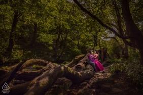 Angleterre images de fiançailles d'un couple assis sur d'énormes arbres et racines | Photographe londonien avant le mariage pour les portraits