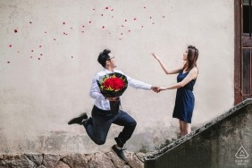 China pre-wedding engagement pictures of a couple having fun in stairs with bouquet of flowers | Fujian portrait shoot