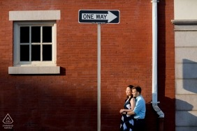 Urban engagement photos of a couple with brick building and street signs | Rhode Island photographer pre-wedding portrait session