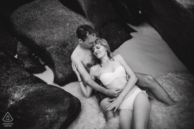 Black and white wedding photographer engagement portrait of a couple on the rocks in the water | NRW pre-wedding pictures