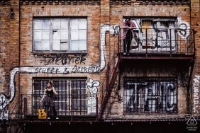 Pomorskie pre-wedding engagement pictures of a couple on fire escape of a graffiti painted building  | Poland portrait shoot