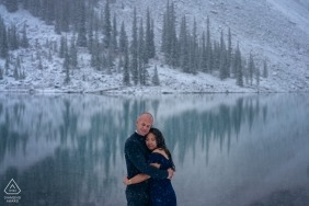 Alberta pre-wedding engagement pictures of a couple near the lake with snow covered mountains and trees | Canada portrait shoot