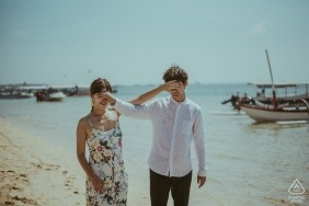 Indonesia engagement pictures of a couple covering each others eyes at the beach with boats  | Bali photographer pre-wedding shoot with photographer
