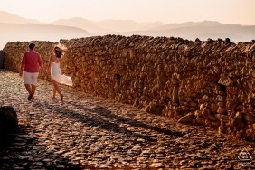 Newly engaged couple walking hand in hand on a cobblestone road during their pre-wedding engagement shoot