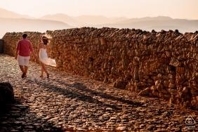 Świeżo zaangażowana para spacerująca w parze na brukowanej drodze podczas sesji zaręczynowej przed ślubem