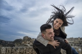 A Calabria engagement photo shoot session of a couple piggy back in the wind | Reggio Calabria wedding photographer