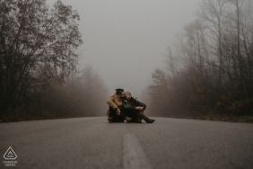 Bulgaria engagement photos of a couple sitting in the middle of a foggy Lovech road  | Lovech photographer pre-wedding portrait session