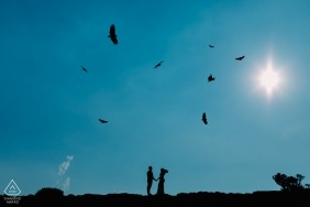Brazil engagement pictures of a couple silhouetted with birds and the sun overhead | Cambara do Sul photographer pre-wedding photo shoot session