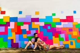 Mines Gerais wedding photographer engagement portrait of a couple against rainbow painted building | colorful pre-wedding pictures