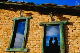 Brazil engagement pictures of a couple silhouetted in window of brick building | Minas Gerais photographer pre-wedding photo shoot session