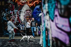 England wedding photographer engagement portrait of a couple with graffiti wall and dog / walker passing by  | Devon pre-wedding pictures