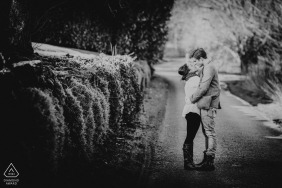 Black and white engagement photos of a couple hugging in a country lane  | Devon photographer pre-wedding portrait session