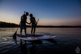 Engaged couple on paddleboards out on the water at sunset in Windham, NH.