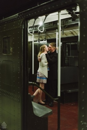 A young woman and man embrace inside an antique New York City subway car.  Engagement Portrait at the New York State Museum