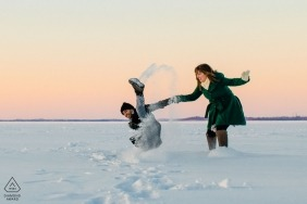 A MN couple runs to warm up as he slips on lake Mendota | Engagement Photography Sessions