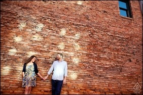 Denver urban engagement photography of couple against red brick building.