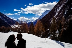 Silhouetted engaged couple in the mountains with snow, blue sky and clouds