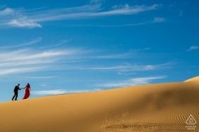 Couple marchant dans les dunes de Glamis pour une séance de fiançailles dans le désert