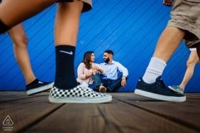 Un couple fiancé est assis sur la jetée de Santa Monica pour la photographie de fiançailles en Californie