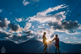 A couple walks along Kootenay Lake as the sun sets during their engagement photo shoot | Nelson BC Wedding Photographer