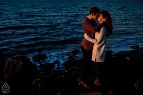 Seattle, Washington Couple kisses on beach near sunset