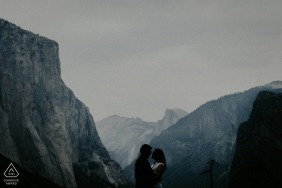 YOSEMITE ENGAGEMENT PORTRAITS WITH BIG MOUNTAINS AND CLIFFS BEHIND COUPLE