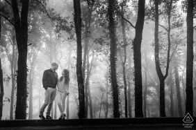 Black and white photograph of couple in a forest with fog | Erice, Sicily Romance in the fog