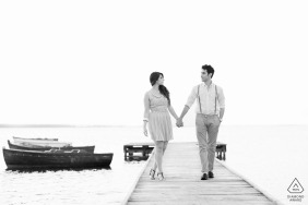 black and white image of two lovers walking on a jetty by the sea | Trapani, Sicily Portraits | hand in hand