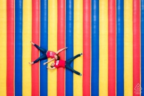 DC Couple laying down on giant outdoor inflatable bounce house floor