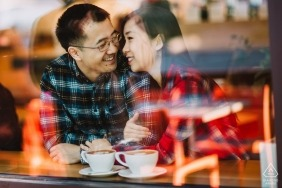 A newly engaged San Francisco couple enjoying a moment together inside a coffee shop as the city is reflected in the class before them