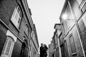 Amiens France newly engaged couple framed in tall city buildings in black-and-white