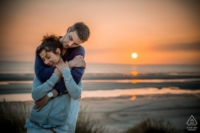 A young beautiful engaged couple embrace in a hug with their backs to the setting sun and the ocean