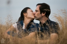 Nordsee, Germany engagement portrait of a couple sitting in tall wispy Grass while kissing