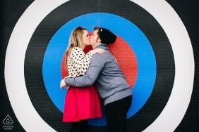 Session de fiançailles créative Puget Sound - Couple s'embrassant devant une grande cible colorée